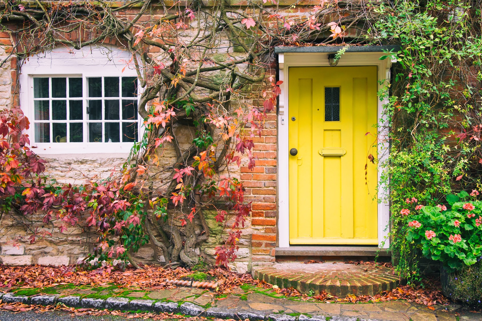 english country home with yellow door in autumn