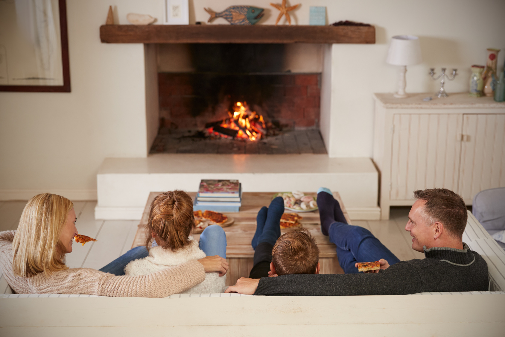 happy family sitting on sofa by fire in living room